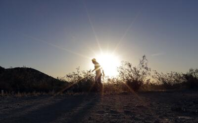 Un hombre camina bajo un intenso sol.