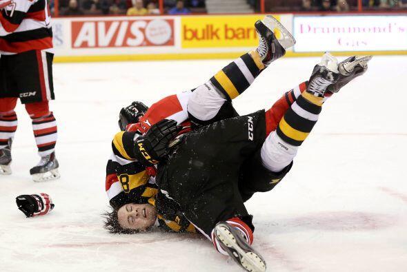 Así embarró sobre el hielo Troy Henley #3 de los Ottawa 67's a Mack Lemm...