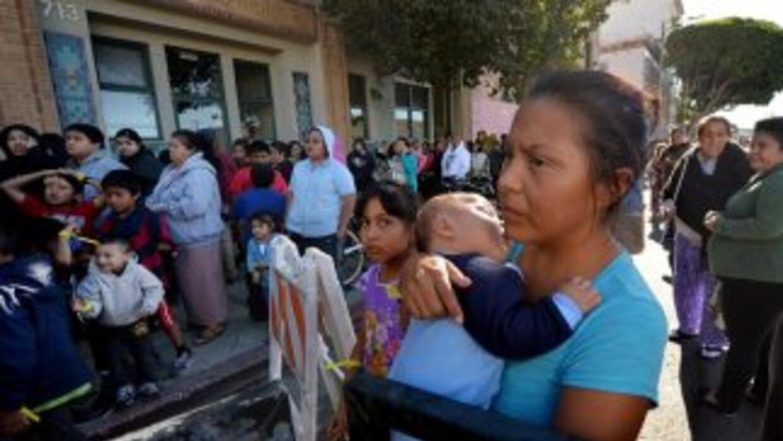 Una madre y su niño esperan durante un evento de caridad realizado en Lo...