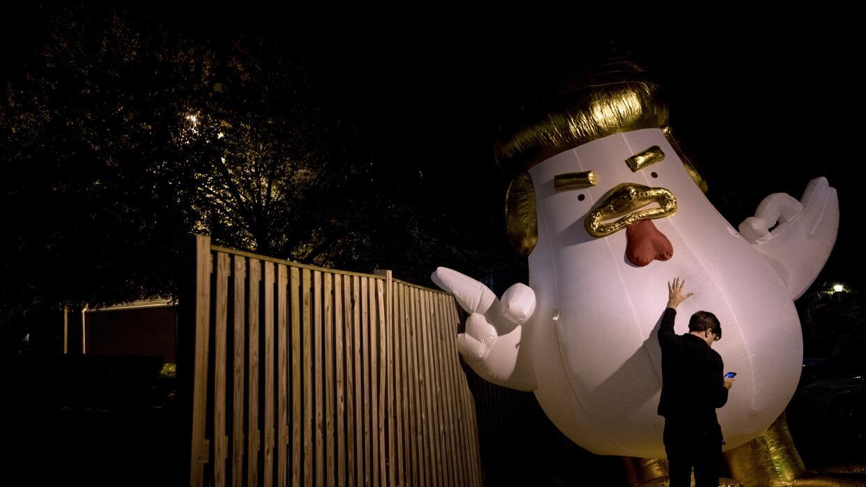 Un demócrata sostiene un muñeco inflable contra Trump en Fairfax, Virginia.