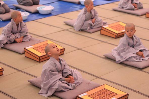 Un grupo de niños rinden honores a Buda.  Se afeitaron la cabeza en el t...