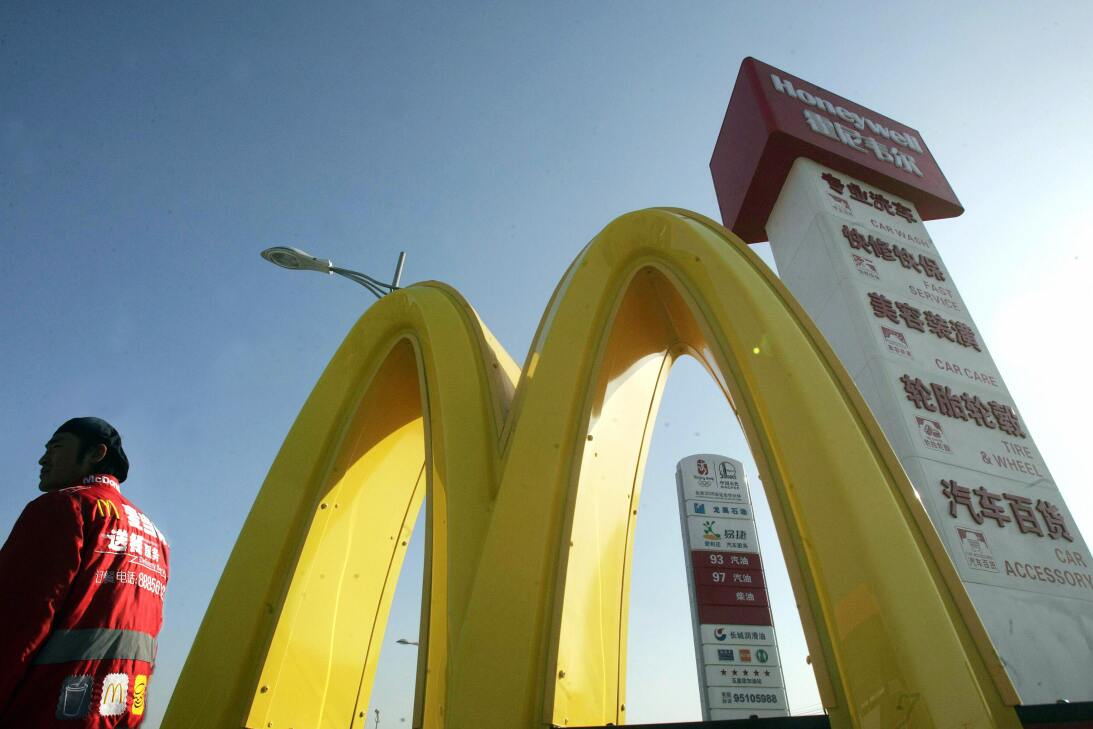 A US fast-food giant McDonald's staff waits outside the latest drive...