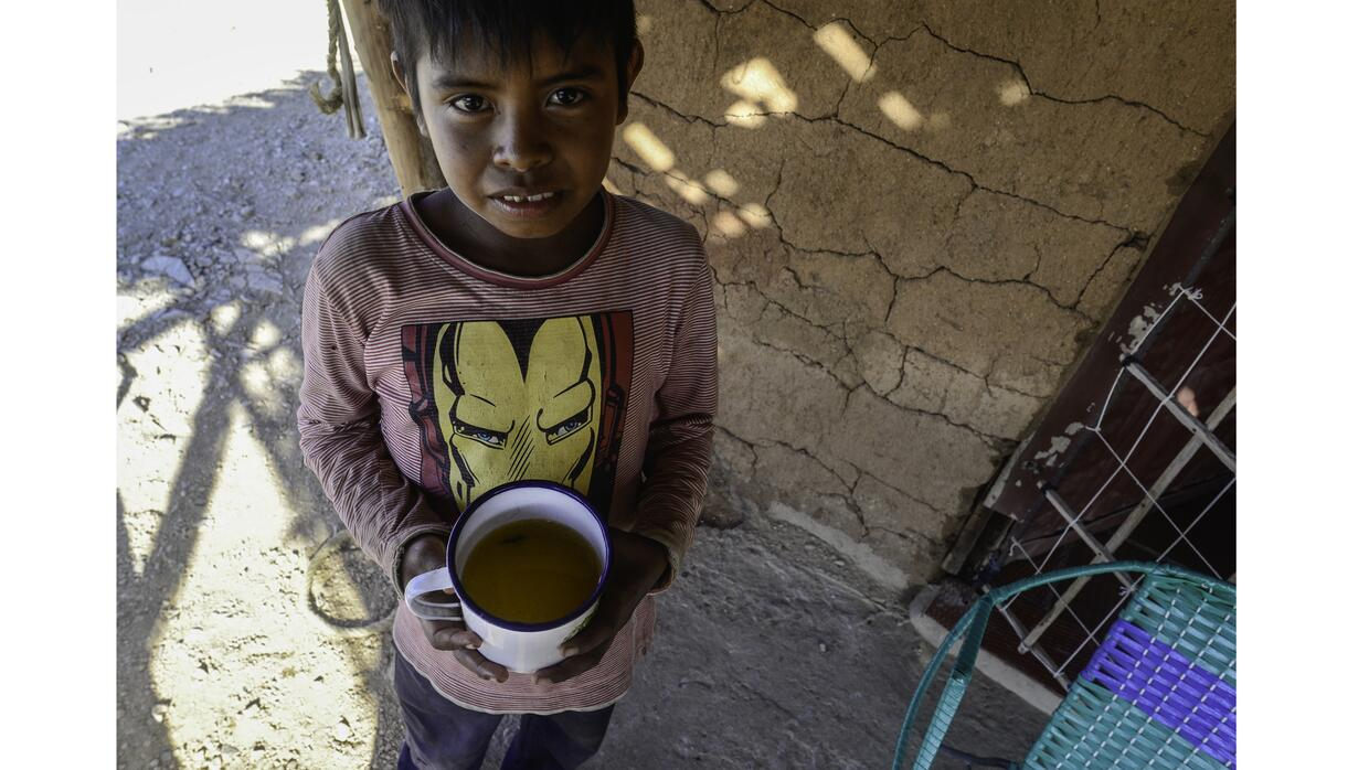 Carlos Jusayu, 11, holds a cup of dirty water from the well nearest to h...