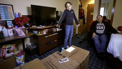 María Reyes, de San Juan,observa a su nieto Edward, en su habitación d...