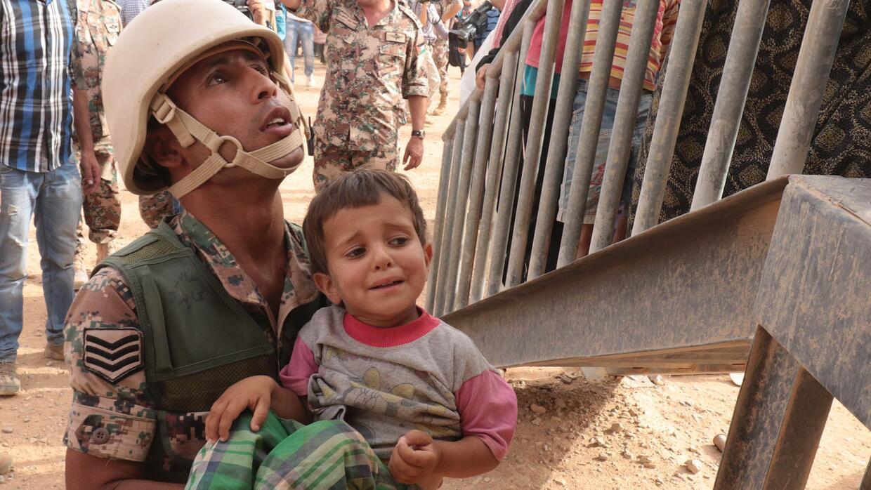 Un soldado jordano carga a un niño sirio en un campo en la frontera