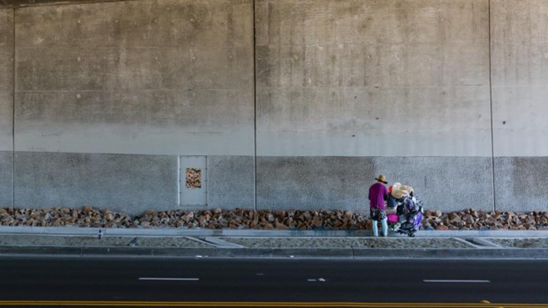 Una mujer sin hogar detiene su carrito de compras enfrente del reci&eacu...