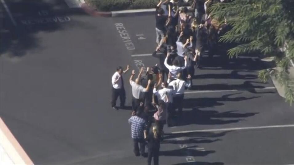Un grupo de personas sale de lugar del ataque con las manos en alto