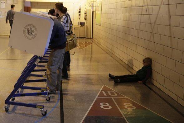 Este pequeño luce abrumado mientras sus padres votan en una casilla inst...