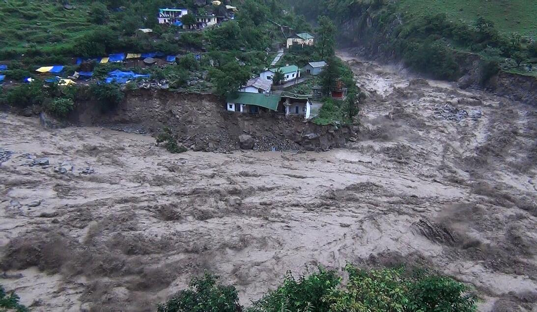 Houses perch precariously as river banks collapse from the rising waters...