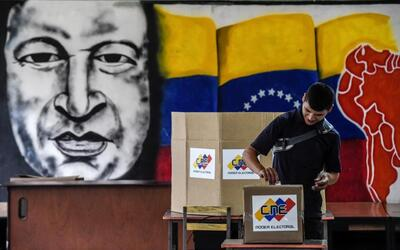A voter casts his ballot in front of a mural of the late President Hugo...