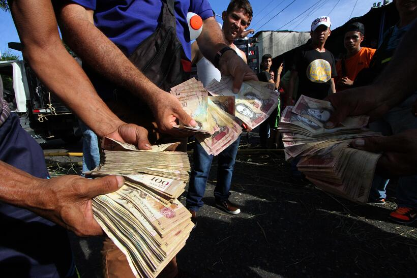 Un grupo de manifestantes muestra los billetes inservibles de 100 bol&ia...