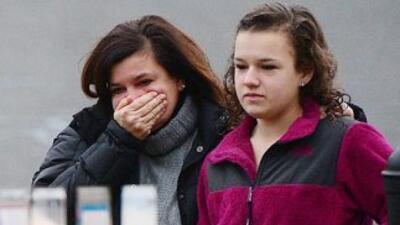 Una mujer llora junto a su hija frente a un altar improvisado en las afu...