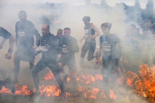 Los deportistas compiten durante el obstáculo fuego de la carrera Tough...