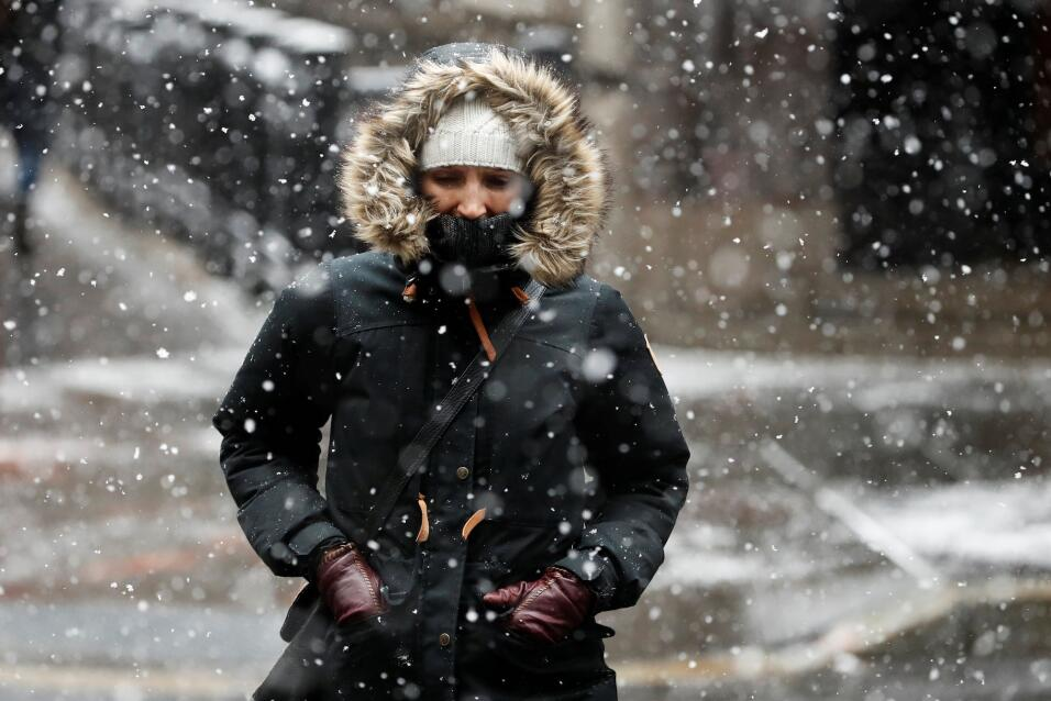 Esta mujer camina por una calle de Nueva York bajo una nevada