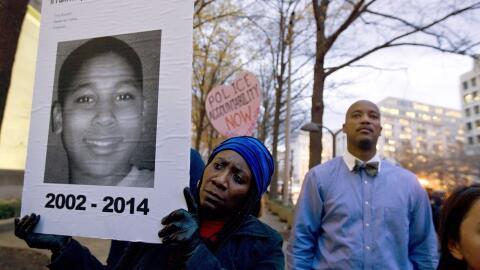 Una mujer sujeta un retrato del joven Tamir Rice, quien murió bal...