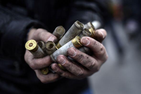 Un hombre muestra los casquillos de balas de grueso calibre disparadas p...