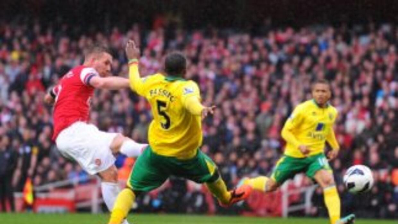 Lukas Podolski dispara para anotar ante Norwich.
