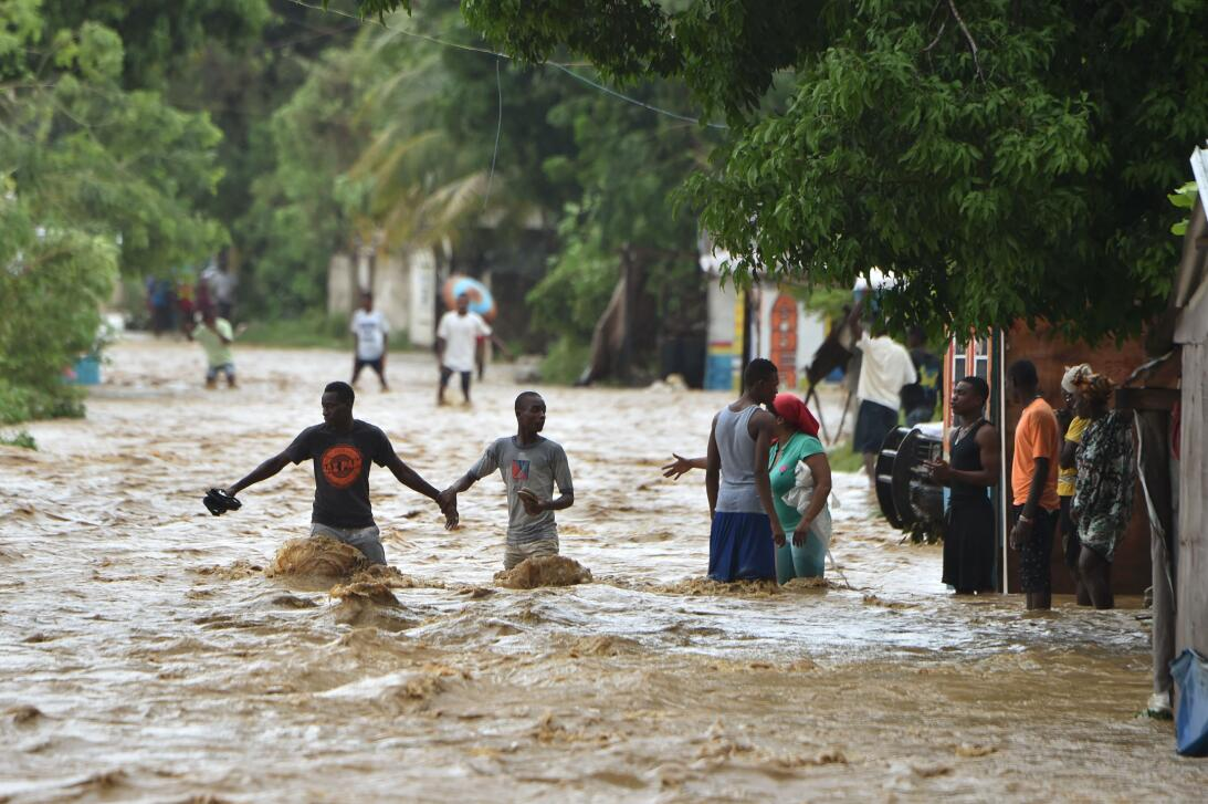 Residents engulfed by a river that burst its banks near Leogane on Haiti...