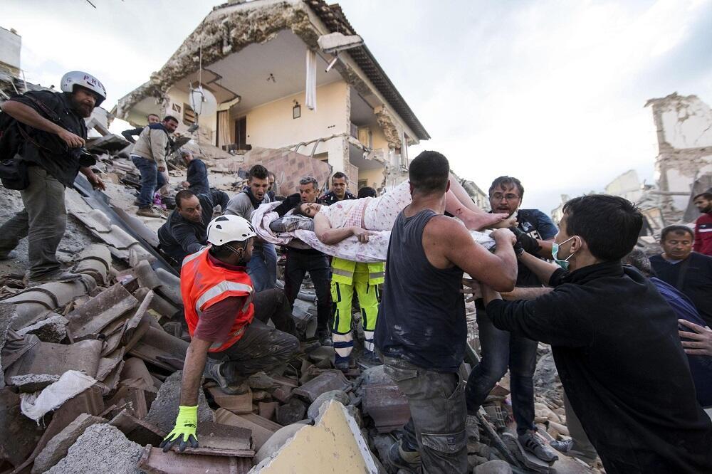 Una mujer es sacada a hombros en una camilla de debajo de los escombros...