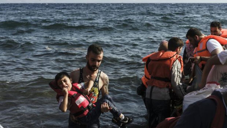 Un refugiado sirio lleva a un niño en la isla de Lesbos.
