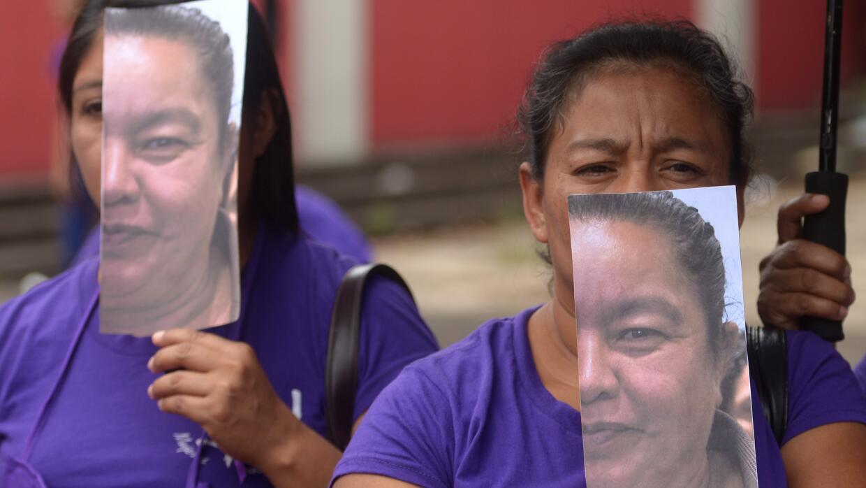 Mujeres llevan imágenes con parte del rostro de la líder comunitaria Aid...