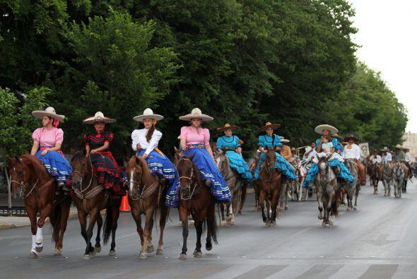 Mujeres vestidas de mujeres revolucionarias marchan sobre sus caballos p...