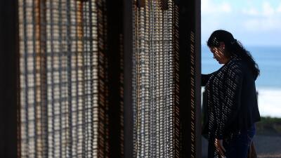 Una mujer frente a la barda metálica que divide la frontera entre Califo...
