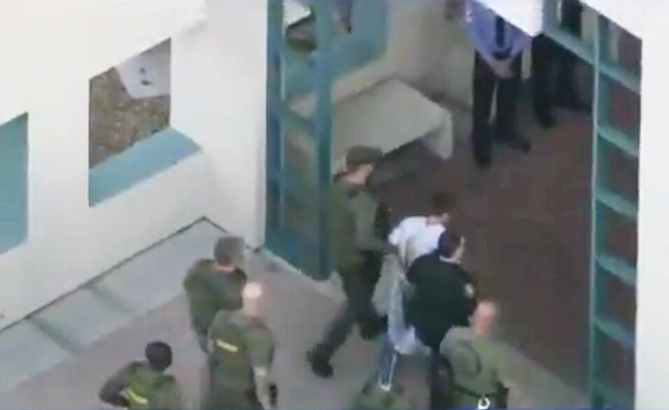 La policía lleva al sospechoso dentro de la cárcel del con...