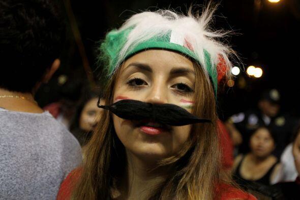 Una de las asistentes a la plaza de Mérida porta una peluca con los colo...