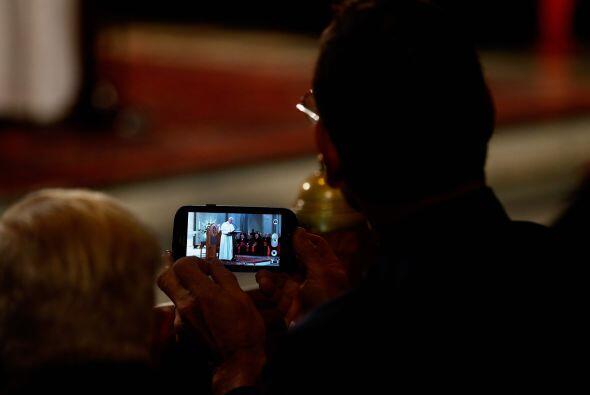Este hombre mira al pontífice a través de su teléfono móvil.