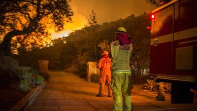 Bomberos de California contemplan cómo las llamaradas del incendio Thoma...