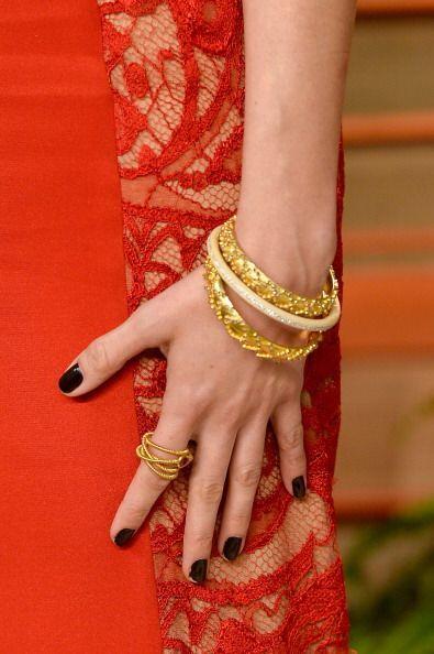 El esmalte en color negro, a juego con prendas coloridas, doradas y plat...
