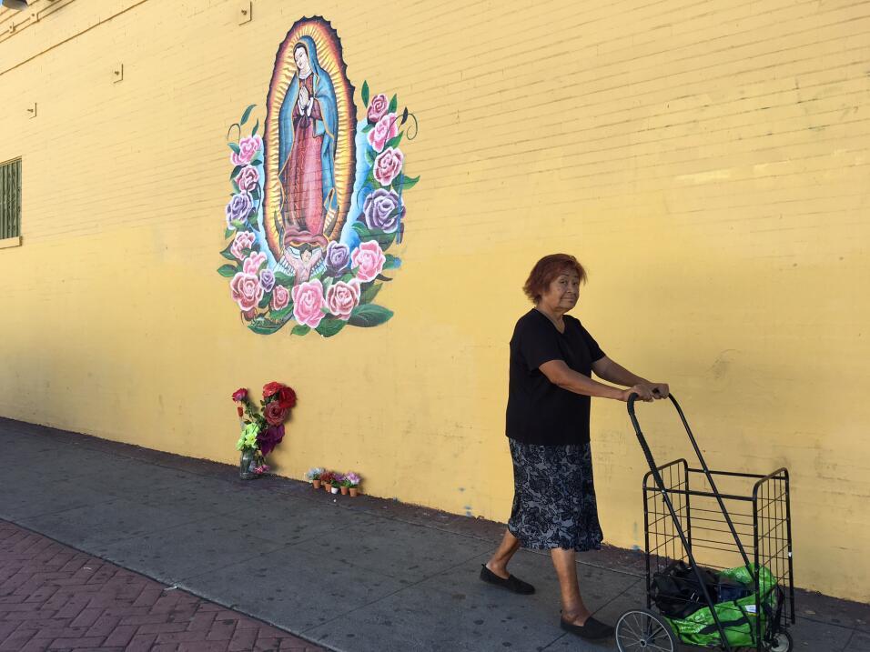 Una mujer camina frente a una imagen de la Virgen en la pared de una lav...