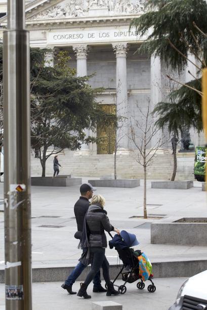 La pareja caminaba unida tomando la carriola de su hijo.