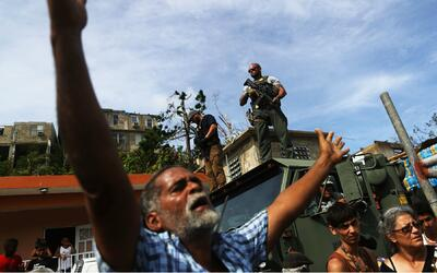 Un hombre pide alimentos durante una repartición vigilada por mil...