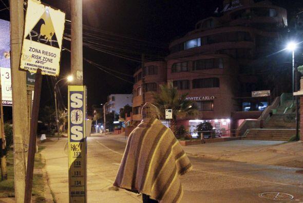 Un hombre camina junto a una señal de alerta de tsunami durante l...