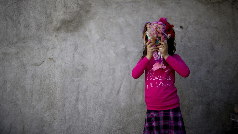 Luana posa para una fotografía con sus muñecas en su casa en Merlo.