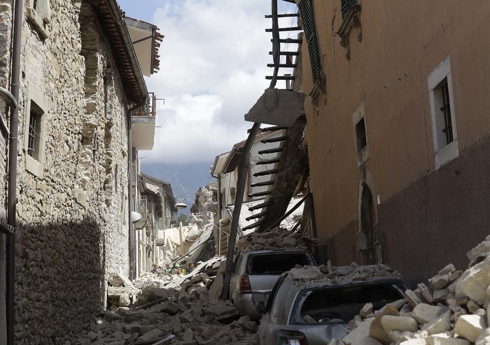 Equipos de rescate entre los escombros de una calle en Amatrice, una de...