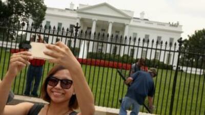 Una turista se hace un selfie frente a la Casa Blanca.