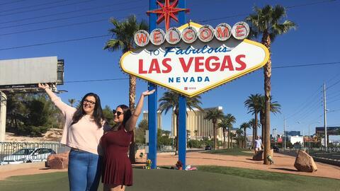 Dos turistas españolas posan sonrientes frente al cartel que da l...