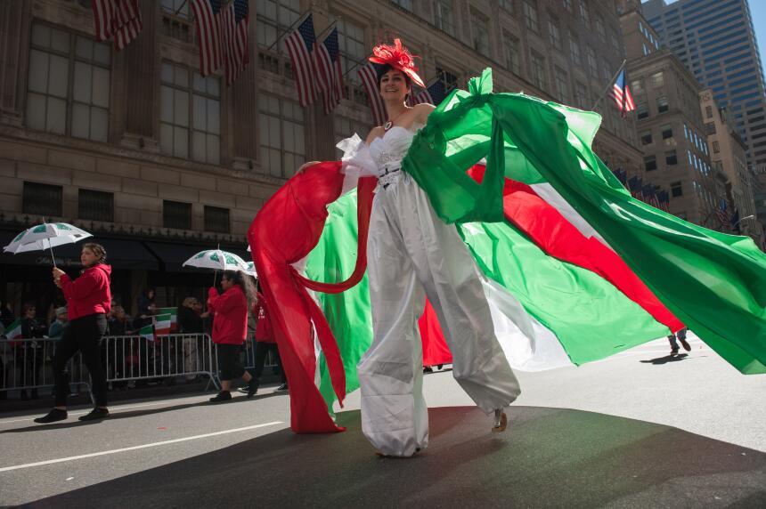 Luciendo los colores que representan a Italia, una joven en zancos desaf...