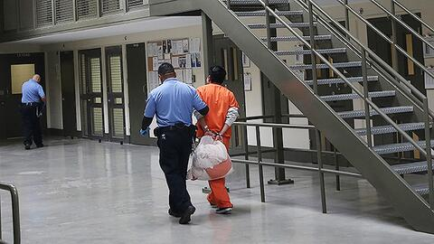 Un guardia traslada a un inmigrante indocumentado detenido en el centro...