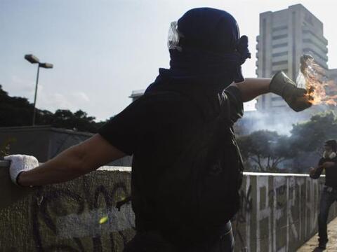 Un manifestante lanza una bomba incendiaria durante enfrentamientos cont...