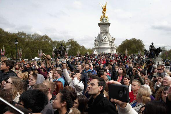 Un puñado de monárquicos envueltos en banderas británicas y turistas cur...