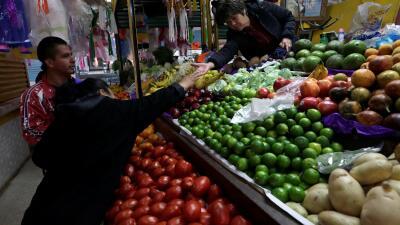 Una mujer compra verduras en un mercado de la Ciudad de México