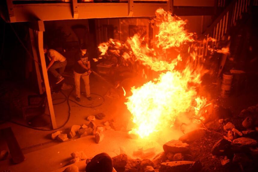 Residentes de La Conchita intentan luchar con el fuego en una de las viv...