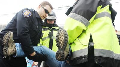 Policías detienen a un manifestante frente a un centro de detención de I...