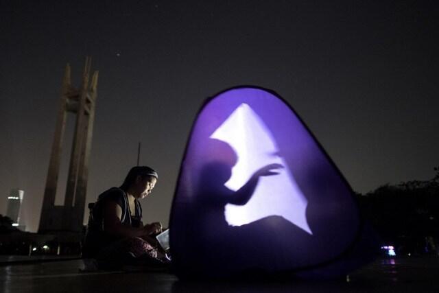 Una persona juega con su sombra en Filipinas en medio de la oscuridad al...