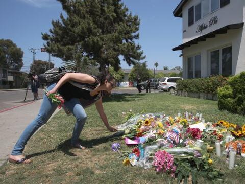 Una mujer coloca flores en el jardín de la casa de la fraternidad...