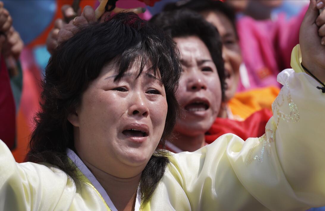 Una mujer norcoreana llora mientras la marcha pasa frente al lugar donde...